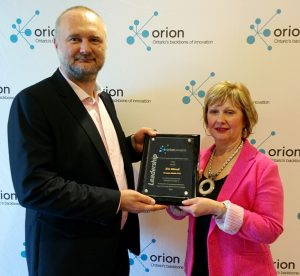 Janine Griffore, Assistant Deputy Minister, French-language, Aboriginal learning and Research division, Ministry of Education, presents Éric Minoli with the ORION 2016 Kindergarten to Grade 12 Leadership Award.