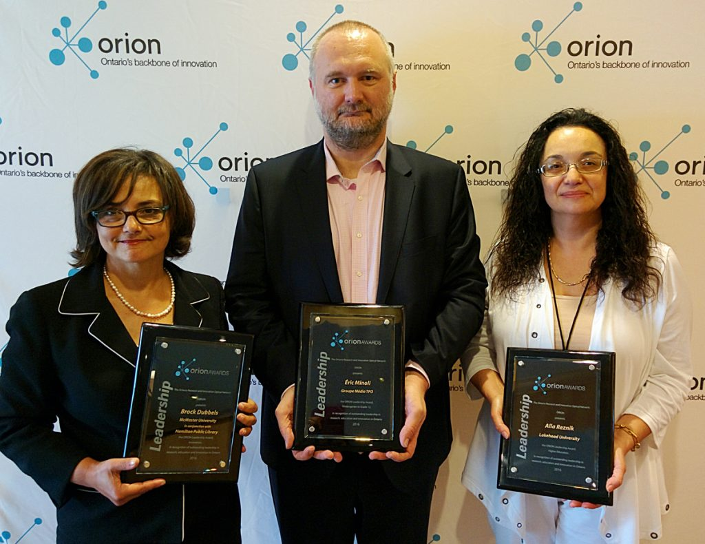 (L-R) Sherry Fahim, accepting on behalf of Brock Dubbels, Éric Minoli, Alla Reznik. Click for hi-res image download.